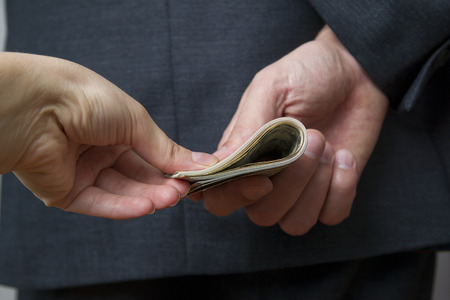 Concept - corruption. Giving a bribe. Money in hand