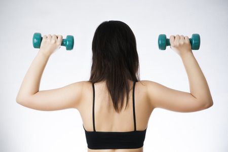Young woman doing exercises with dumbbells on grey background. photo