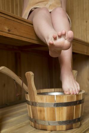 young girl barefoot: Beautiful female legs in sauna, bath accessories. Wooden bucket