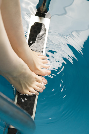 Beautiful female feet on the steps of the pool. photo