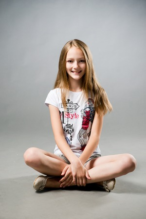 Portrait of a beautiful girl on a gray background in studio.