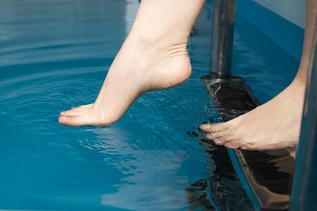 Beautiful female feet on the steps of the pool. Фото со стока - 38568844