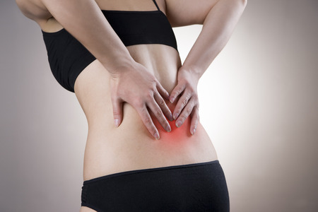 Pain in back of women on gray background. Caring for the female body. Red dot Stock Photo