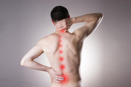 Schmerzen in einem Körper des Mannes auf grauem Hintergrund. Red dot