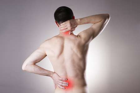 chronic back pain: Pain in the back and neck in men on gray background. Red dot Stock Photo