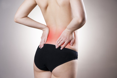 Pain in lower back of women on gray background. Caring for the female body. Red dot photo