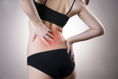 Pain in back of women on gray background. Caring for the female body. Red dot photo