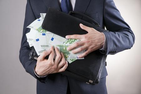 dinero euros: Hombre de negocios con un maletín lleno de dinero en manos de sobre fondo gris Foto de archivo