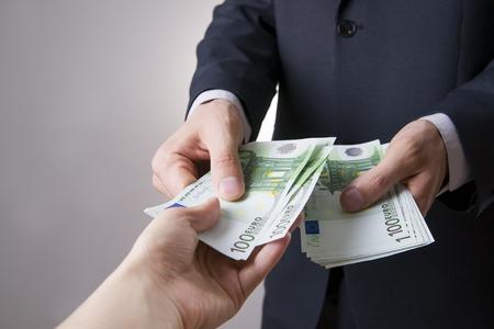 人の手にお金を。灰色の背景にユーロをカウントするには 写真素材