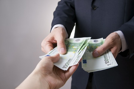 Money in the hands of the people. To count euro on gray background