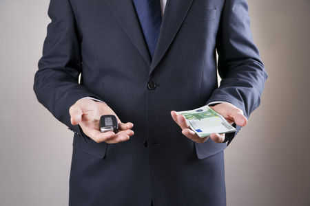 Businessman using car key and money. Keyless in male hand photo