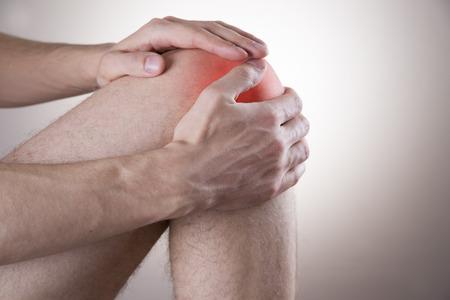 dolor de rodilla: El dolor de rodilla en los hombres en el fondo gris