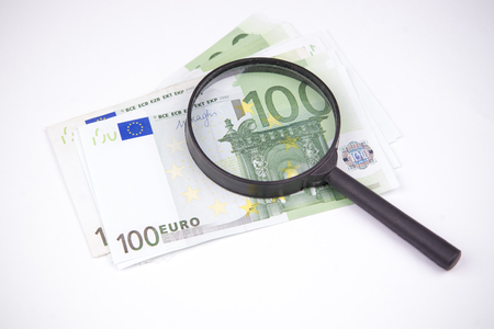 inspected: Banknotes hundred euros on a white background. Inspected with a magnifying glass