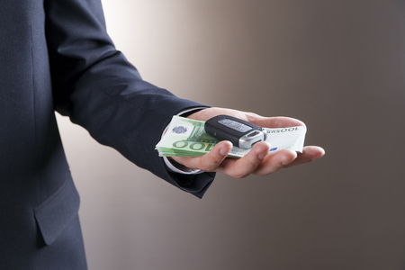 keyless: Businessman using car key and money. Keyless in male hand Stock Photo