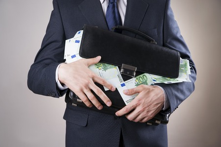 money concept: Businessman with a briefcase full of money in the hands of on gray background