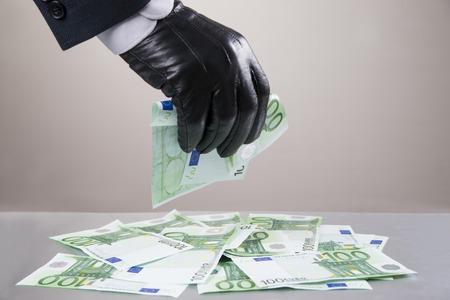 개념 - 부패, 도난. 돈을 훔치기 위해 고안된 장갑 leathern에 손을.