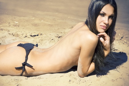 topless brunette: Smiling beautiful young brunette woman sunbathing topless on a beach Stock Photo