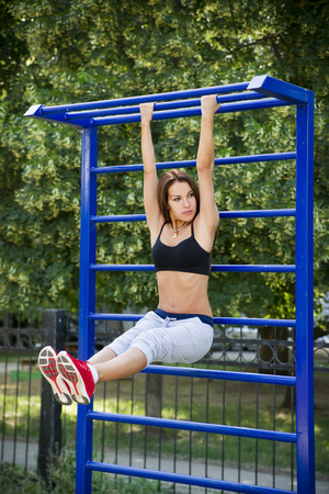 abdominal wall: Beautiful young woman on the sports ground. Exercise outdoors