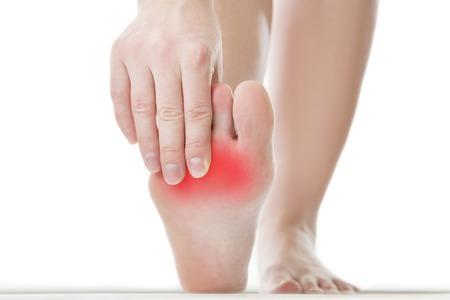 tacones rojos: El dolor en el pie. Masaje de pies femeninos. Pedicuras. Aislado en el fondo blanco.