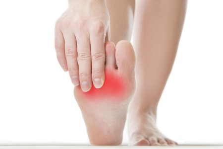 red heels: Pain in the foot. Massage of female feet. Pedicures. Isolated on white background. Stock Photo