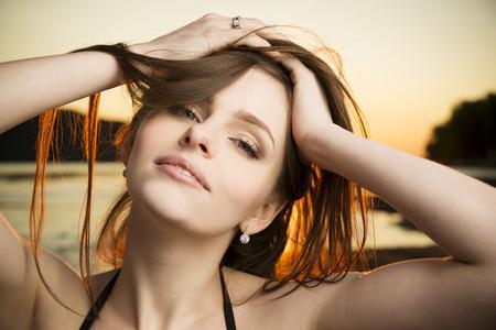 bikini slender: Beautiful woman in bikini on sunset background. Slim girl posing in a swimsuit Stock Photo