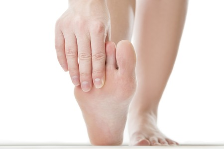 Massage of female feet. Pedicures.Pain in the foot.  Isolated on white background. Stock Photo