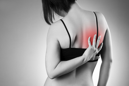 muscle women: Woman with backache. Pain in the  human body. Black and white photo with red dot
