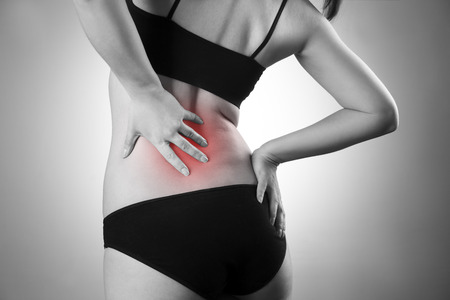 Woman with backache. Pain in the  human body. Black and white photo with red dot Фото со стока - 42300421