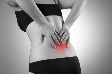 Woman with backache. Pain in the  human body. Black and white photo with red dot