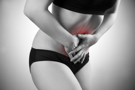 griping: Woman with abdominal pain. Pain in the  human body. Black and white photo with red dot