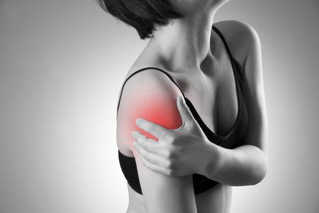 hombros: Mujer con dolor en el hombro. El dolor en el cuerpo humano. Foto en blanco y negro con el punto rojo Foto de archivo
