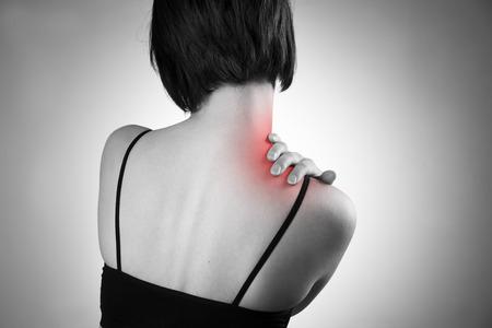 肩の痛みを持つ女性。人間の体の痛み。赤のドットの黒と白の写真 写真素材