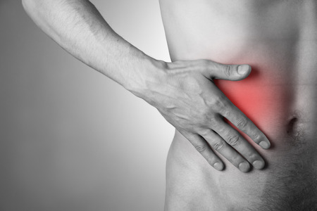 griping: Pain in the right side. Attack of appendicitis. Red dot. Stock Photo