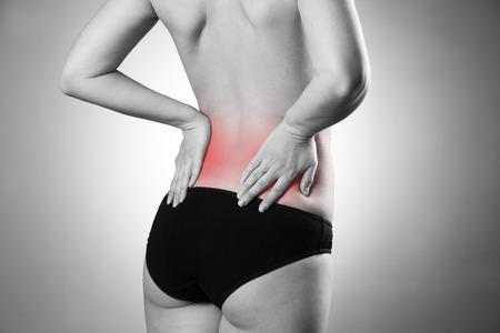 背中の痛みと女性。人間の体の痛み。赤い丸印で黒と白の写真