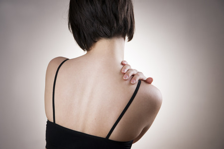 Woman with pain in shoulder. Pain in the  human body on gray background