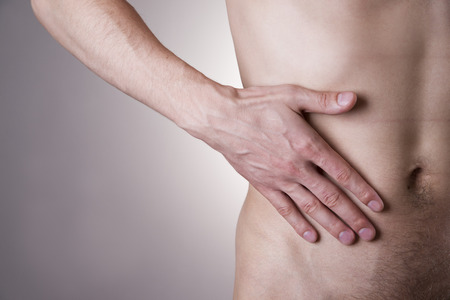 appendicitis: Pain in the right side. Attack of appendicitis. Man on a gray background