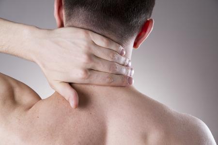 hombros: Dolor en el cuello. Hombre con dolor de espalda. Dolor en el cuerpo del hombre sobre un fondo gris Foto de archivo