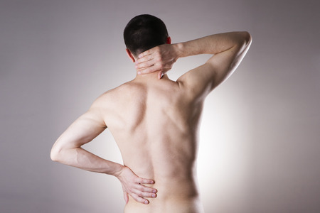 nude male body: Man with backache. Pain in the mans body on gray background