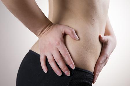 ovario: Dolor en el cuerpo de la mujer sobre fondo gris. El ataque de apendicitis