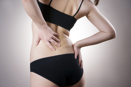 背中の痛みと女性。灰色の背景に人間の体の痛み 写真素材