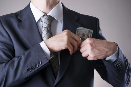 remuneraciones: Hombre de negocios con el dinero en el estudio sobre un fondo gris. Concepto de la corrupción