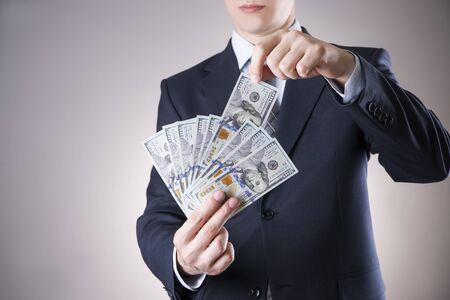 remuneración: Hombre de negocios con el dinero en el estudio sobre un fondo gris. Concepto de la corrupción