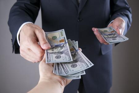 corrupcion: Hombre de negocios con el dinero en el estudio sobre un fondo gris. Concepto de la corrupción