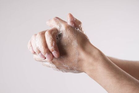 on hands: A man washes his hands with soap and water on a gray background