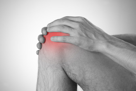 stretching condition: Pain in the knee on a gray background