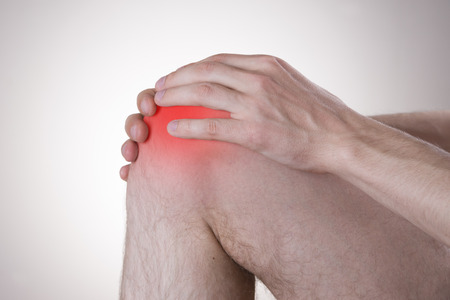 Pain in the knee on a gray background