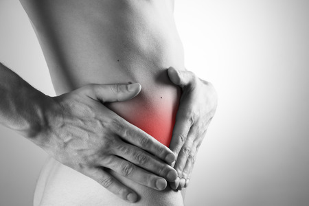griping: Attack of appendicitis. Pain in the right side of the man. Pain in a mans body on a gray background Stock Photo