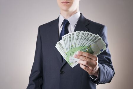 corruptible: Businessman with money in studio on a gray background. Corruption concept