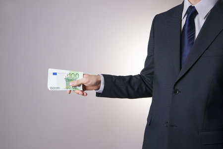 venality: Businessman with money in studio on a gray background. Corruption concept