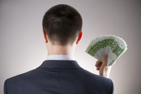 Businessman with money in studio on a gray background. Corruption concept Фото со стока - 43156580